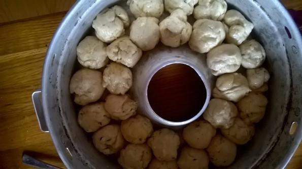 Обминаем тесто. Смазываем руки подсолнечным маслом и делаем из теста шарики, размером с грецкий орех. Обмакиваем каждый шарик в душистом масле, и укладываем в форму. У меня - старенькая, еще бабушкина.